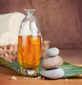 Massage oil and zen stones — Stock Photo