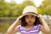 Little girl pulling down her hat — Stock Photo
