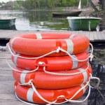 Group red life buoy on lake bridge — Stock Photo #11911128