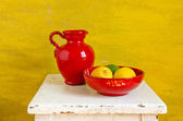 Red ceramics jug and plate with lemons — Stock Photo