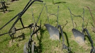 Historical horse and manual plows collection in farm garden