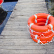 Life buoy on wooden resort lake bridge — Stock Photo