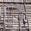 Ancient wooden etnographic barn wall with tools — Stock Photo #13492872
