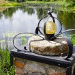 Stock Photo: Original lamp on millstone near pond