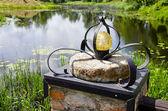Original lamp on millstone near pond — Stock Photo