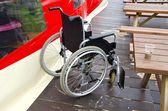 Sedia a rotelle vuota invalidi in mare beach café — Foto Stock