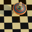 Wooden whirligig rotate on chessboard — Stock Video