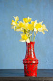 Red vase on table with spring narcissus — Stock Photo