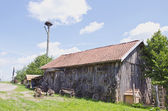 Old barn in farm with carriage wheel — Stock Photo