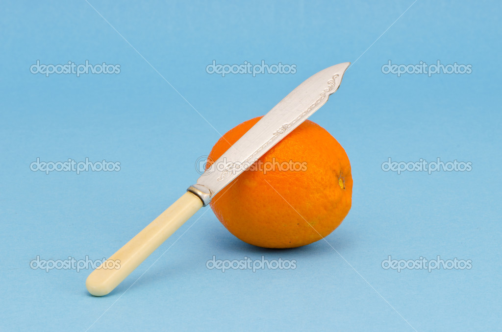 Orange fruit with antique knife on azure background  Stock Photo #13624481