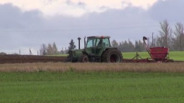 Tractor with sowing machine on field — Stock Video