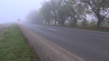 Autumn road with red truck and morning fog — Stockvideo