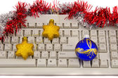 Computer keyboard fragment with Christmas toys on white — Stock Photo