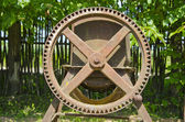 Old agriculture metal wheel in garden — Stock Photo