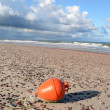 Orange buoy on sea beach sand — Stock Photo
