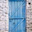 Blue wooden door on white brick wall — Stock Photo