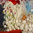 Glass and camel bone jewelry in street market, India - Stock Photo