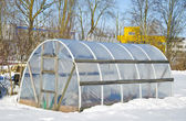 Handmade polythene greenhouse for vegetable in winter on snow — Stock Photo