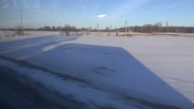 Passenger bus shadow near road on winter field — Vidéo