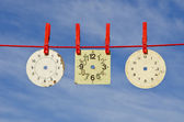 Three ancient clock dial on red string — Stock Photo