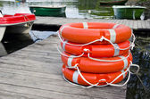 Group orange lifebuoy on wooden resort lake pier — Stock Photo