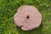 Old cracked millstone on grass — Stock Photo