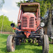 Stock Photo: Old red tractor on grass in farm