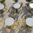Street cafe tables and chairs on pavement — Stock Photo