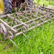 Stock Photo: Tractor on farm field gras with metal harrow