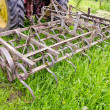Tractor on farm field gras with metal harrow — Stock Photo