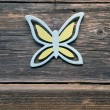 Decorative wooden butterfly on old farm wall — Stock Photo