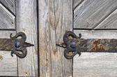 Wrought iron door hinge on old wooden background — Stock Photo