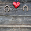 Two rusty horseshoe and heart symbol on wooden wall — Stockfoto