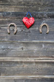 Two rusty horseshoe and heart symbol on wooden wall — Photo