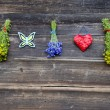 Hanging medical herb bunch and red heart on wall — Stock Photo