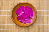Wild rose eglantine petals in wooden plate — Stock Photo