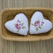 Stock Photo: Handmade two clothes heart symbol in wicker plate