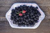 Blackberry ve seramik tabak içinde iki kırmızı ahududu — Stok fotoğraf