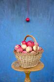 新鮮なリンゴのバスケットとブルーの壁のある静物 — ストック写真