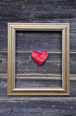 Golden picture frame on old wooden wall and heart — Foto Stock