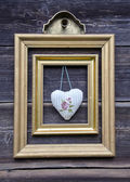 Golden picture frame on wooden wall and cloth heart — Stock fotografie