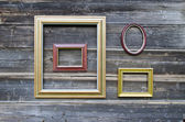 Various picture frame on old wooden wall — Stock Photo