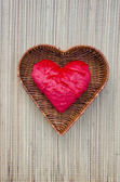 Red cloth heart symbol in wicker basket — Stock Photo