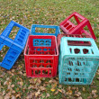 Corlorful plastic boxes for beer bottles on autumn meadow — Stock Photo