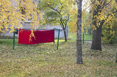 Autumn in city park and red cloth on string — Stock Photo