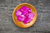 Wild rose brier petal in wooden plate — Stock Photo