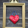 Vintage golden picture frame with red heart on wall — Photo