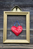 Vintage golden picture frame with red heart on wall — Stock Photo