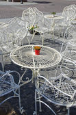 White ornate metal furniture in street restaurant — Stock Photo