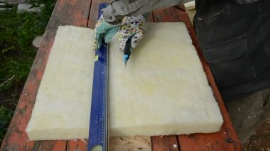 Worker with knife cutting rockwool for house insulation — Vídeo stock